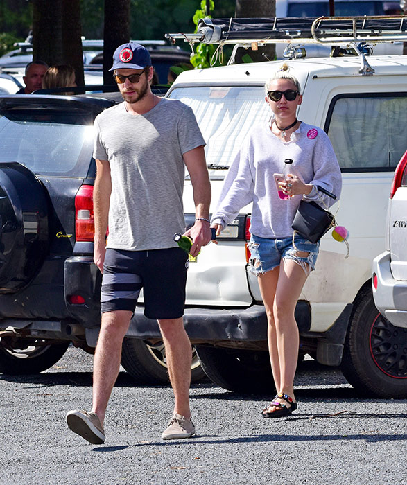 Chris Hemsworth and Miley Cyrus in sunglasses and casual clothing in parking lot