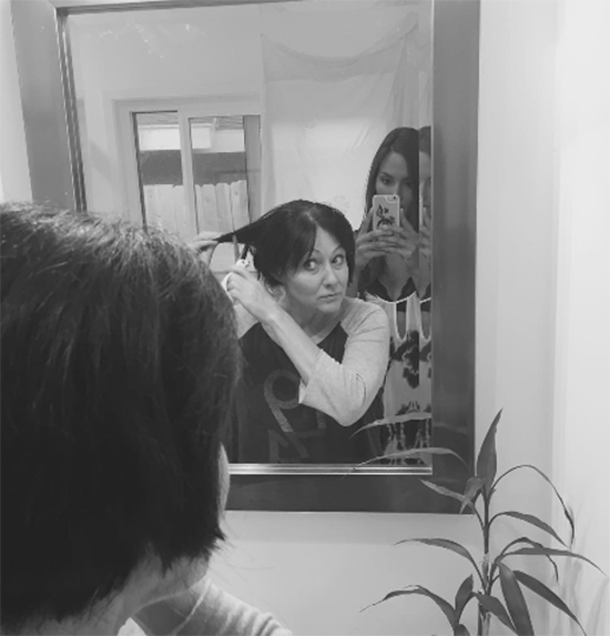 Shannen cutting her hair in the mirror to prepare for shaving her head in Instagram