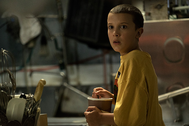 Millie Bobby Brown as Eleven displaying a look of shock as she is displayed in her shaved hair