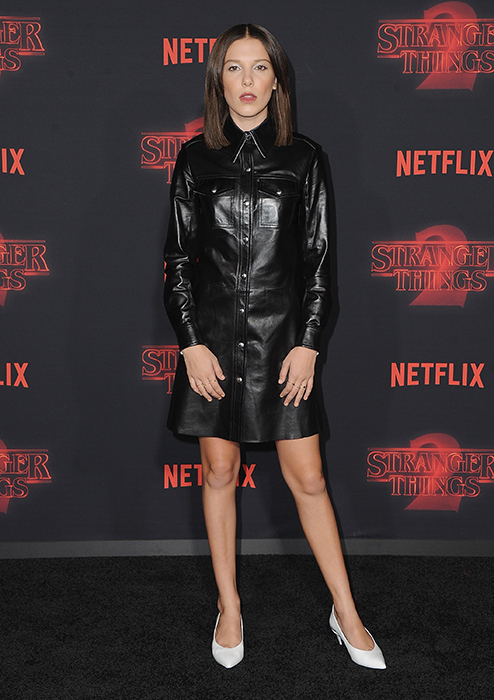Millie Boby Brown with her long dark hair in a black shiny long sleeve dress at the promo of Stranger Things 2