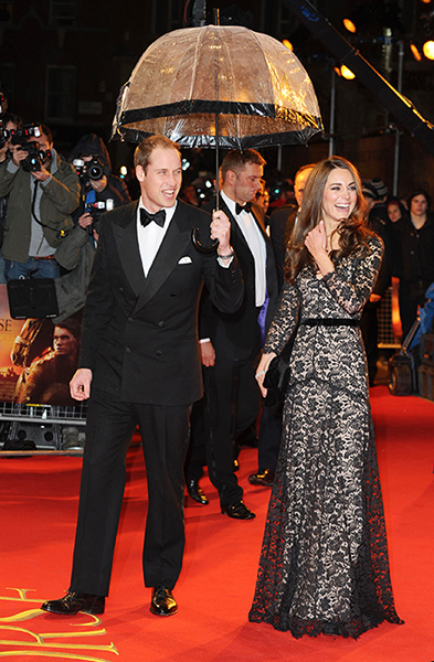 Prince William and Kate Middleton on red carpet while William is seen holding up an umbrella