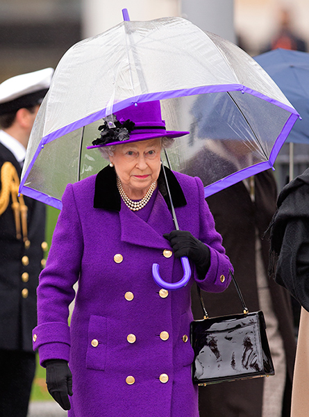 The Queen is holding a purple trim umbrella to match her purple ensemble