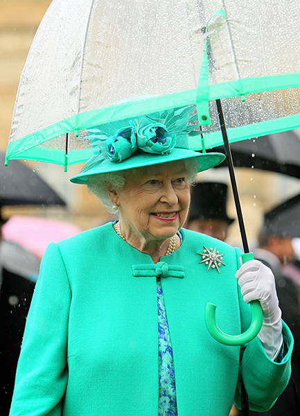 The Queen is holding a green trim umbrella to match her green ensemble