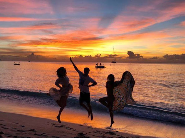 Viscount and Viscountess Weymouth and friends on the beach of Barbados jumping for joy as the sun sets