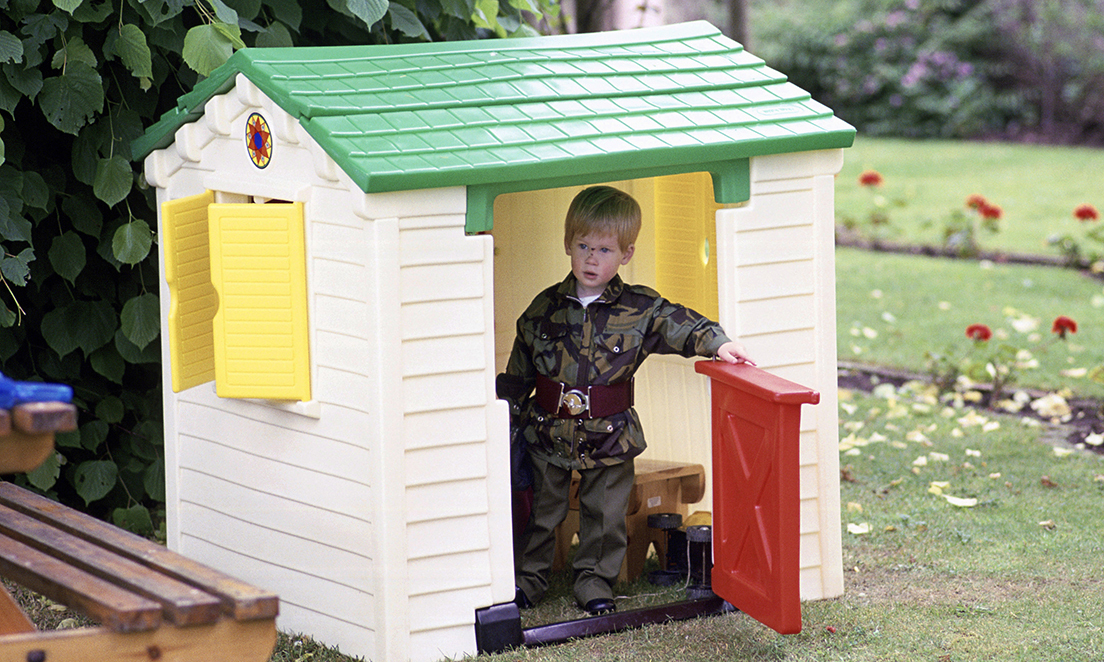 Prince Harry wearing a miniature Parachute Regiment uniform playing in a playhouse in the garden of  Highgrove House     (Photo by Tim Graham/Getty Images)
