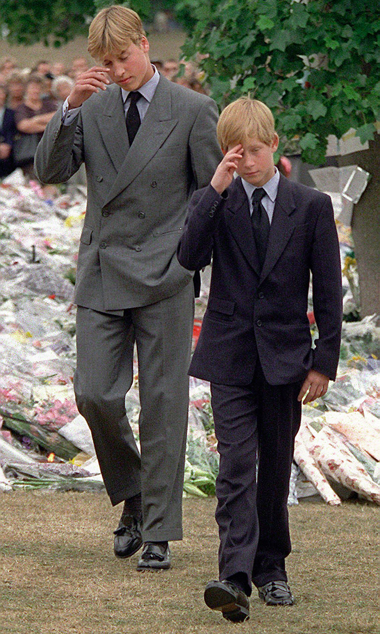 Prince William and Prince Harry gesture after they arrived at Kensington Palace to view some of the flowers and mementos left in memory of their mother Princess Diana. Her funeral was the following day at Westminster Abbey   (Photo By David Brauchli/Getty Images)