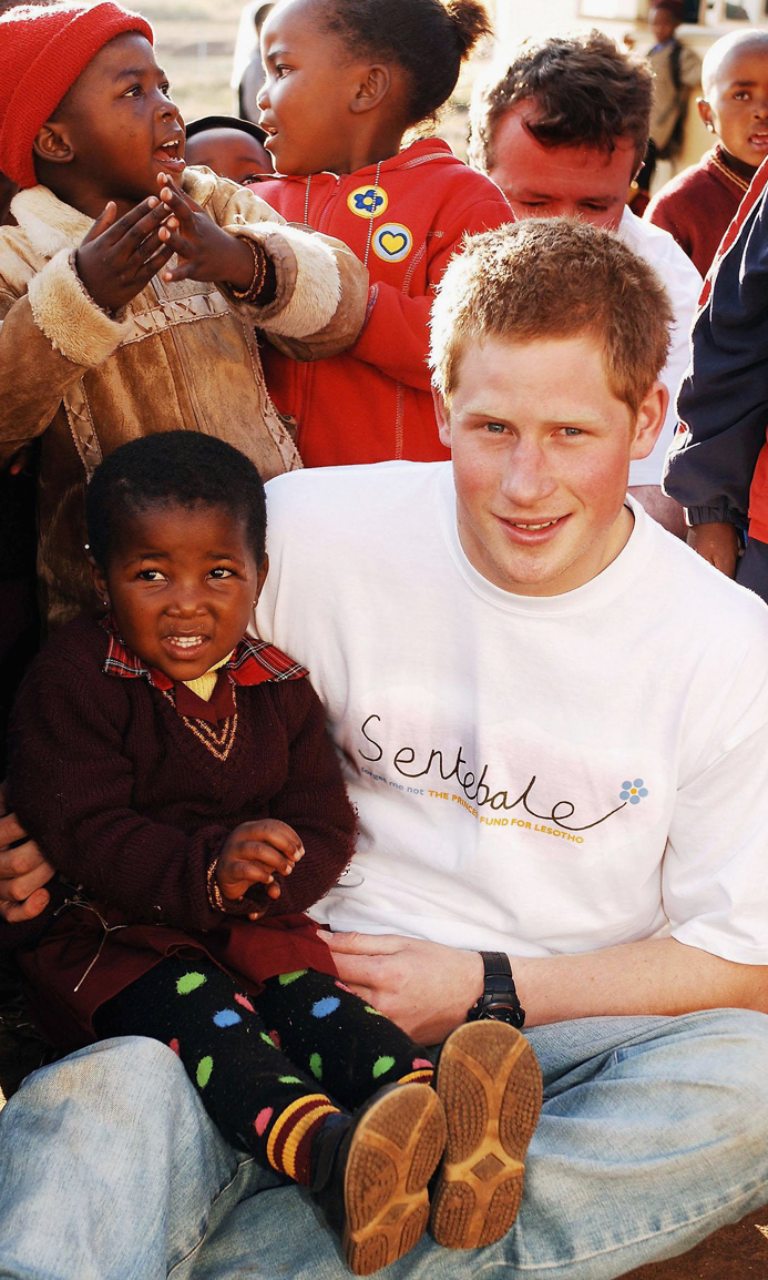 Prince Harry holds a small girl  on a visit to the Good Shepherd home, while on a return visit to Lesotho . The Prince was in the country to launch his new charity called 'Sentebale', which means 'Forget me not' in memory of his mother Princess Diana.