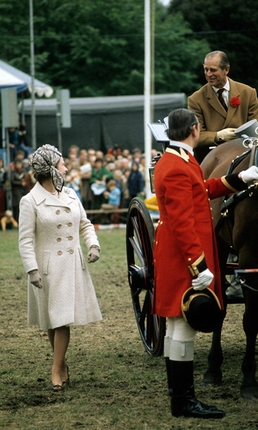 Queen Elizabeth encourages her husband as he takes part in a carriage driving competition at the Windsor Horse Show in May 1974.
