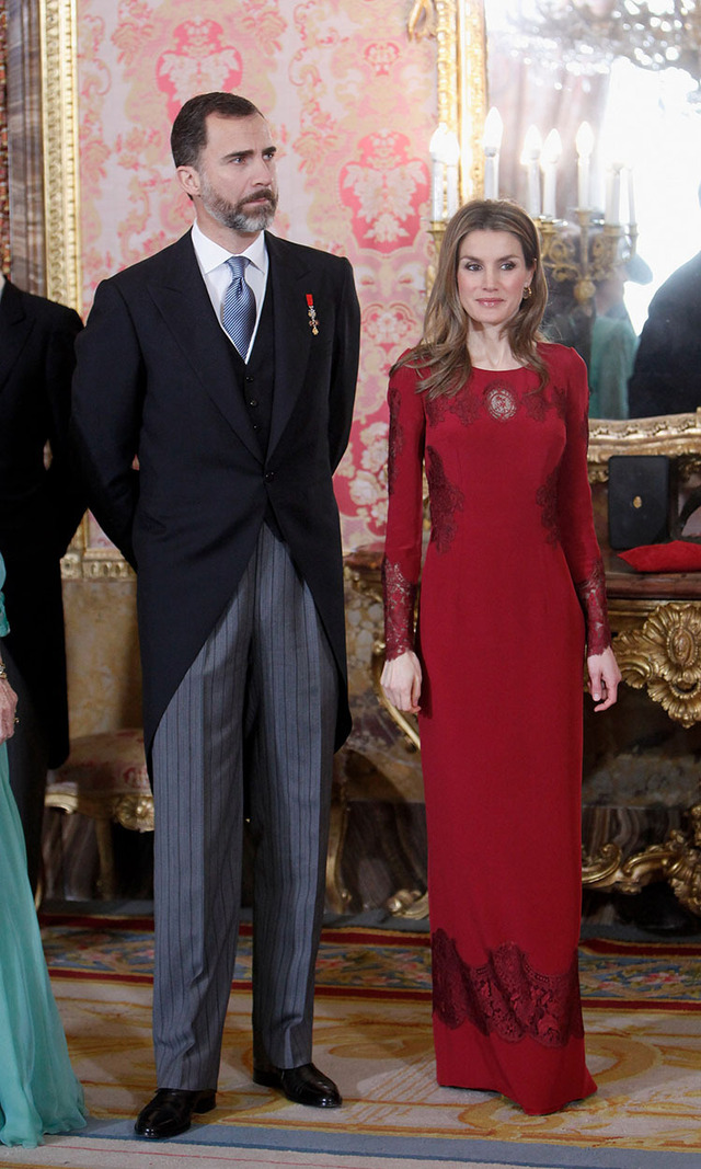How can then-Prince Felipe of Spain not be smiling standing next to then-Princess Letizia and her stunning crimson column gown? While the beauty keeps things modest with long sleeves and a high neckline, the lace detailing and jewelled sleeves lend the look a bit of a party vibe. Hello holiday gala!