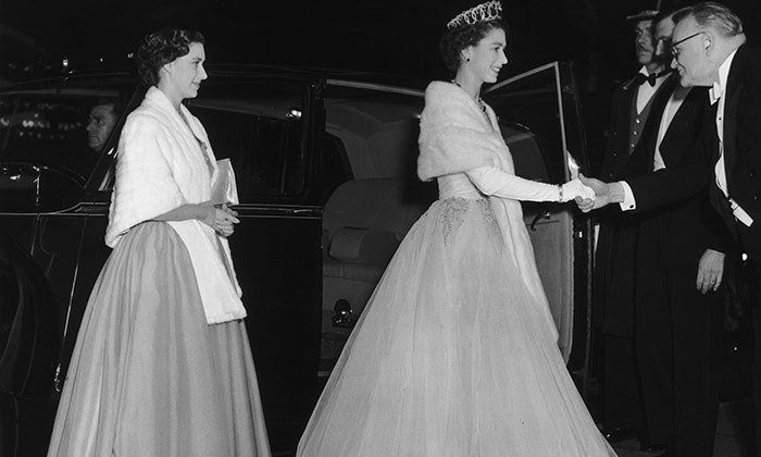 Queen Elizabeth II and her sister Princess Margaret arrive at the Empire Theatre, Leicester Square, London, for the Royal Command Film Performance of 'Beau Brummel', starring Elizabeth Taylor, on November 16, 1954.