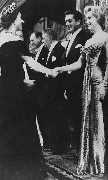 Queen Elizabeth II shaking hands with Marilyn Monroe who stands next to Victor Mature at a Royal Film Performance of 'The Battle of the River Plate' at the Empire Theatre, Leicester Square, London, October 29, 1956.