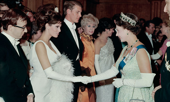 Also in attendance at the 1966 Royal Command Performance, American actress Raquel Welch shaking hands with Queen Elizabeth II. Next in line is the American comedian, writer and director, Woody Allen.