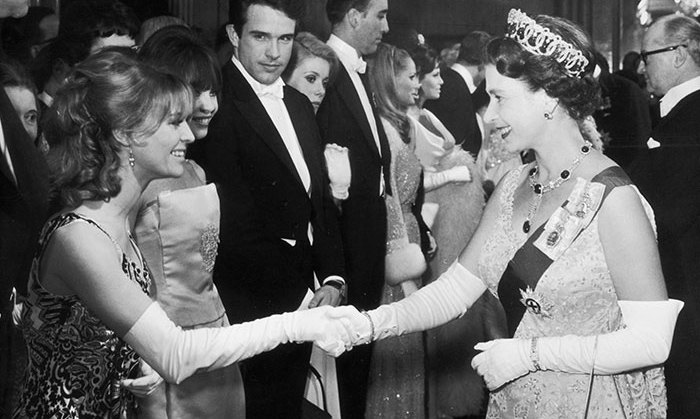 Queen Elizabeth II meets actress Julie Christie before the premiere of 'Born Free' at the Odeon Theatre Leicester Square, London, March 15, 1966. Warren Beatty looks on.
