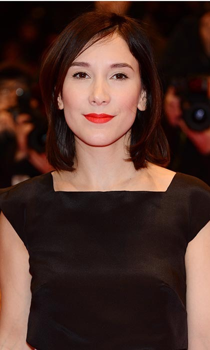 German actress Sibel Kekilli wears her naturally curly hair pin-straight on the red carpet, adding a pop of brightly-coloured lipstick to complement her porcelain skin.
