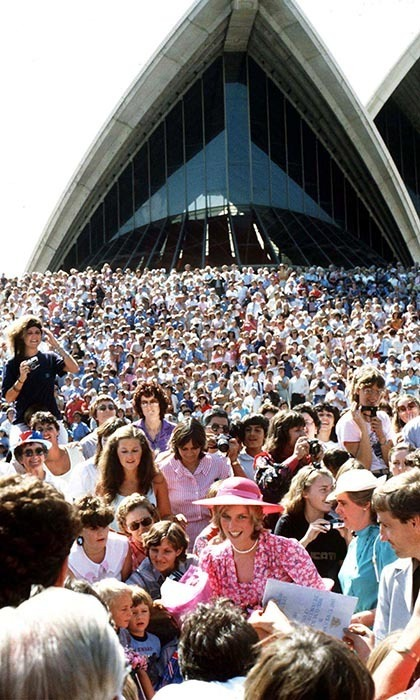 The iconic Sydney Opera House stood overshadowed by a pink floral-clad Diana, Princess of Whales, as throngs of admirers gathered to welcome her. The style icon topped her Belville Sassoon ensemble with a complimentary hued hat by John Boyd.