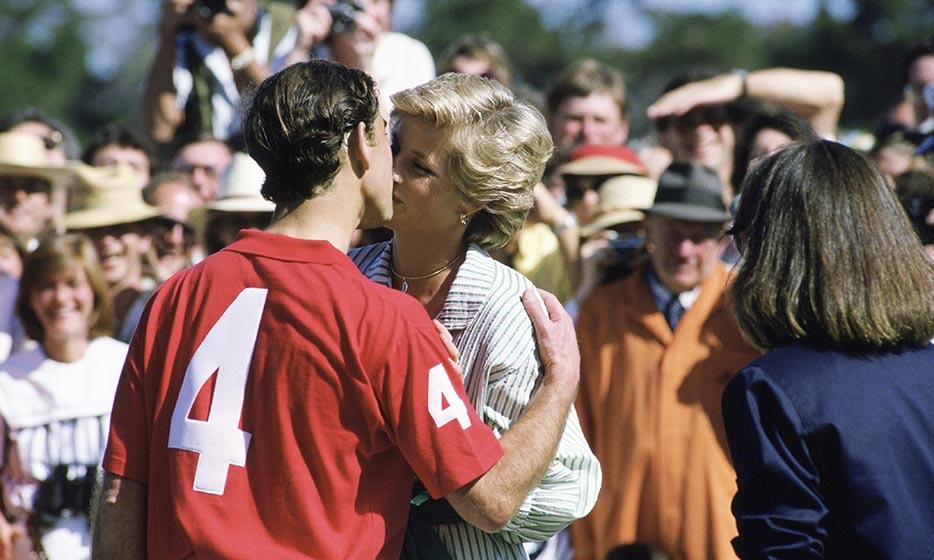 Taking a break from participating in a Melbourne polo match, Prince Charles lays a kiss on his pretty wife on Nov. 3, 1985.