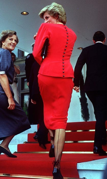The Princess of Wales looked every inch the sultry secretary on a visit to parliament in Camberra in 1988, pairing a red suit buttoned down the back with seamed tights featuring ankle bows.