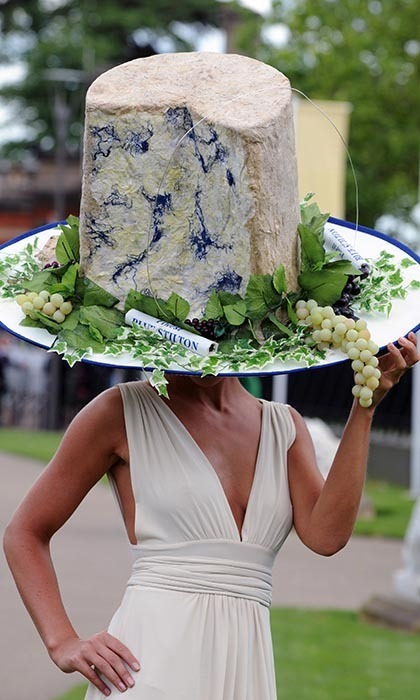 A fromage fiend wore an oversized hat shaped like blue stilton cheese. 