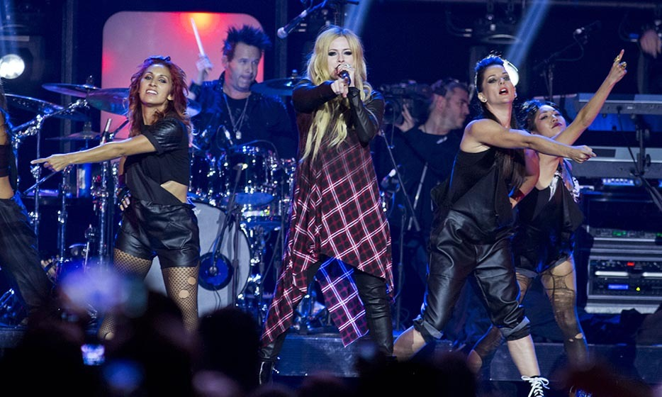 "Rocking leather pants and a pink tartan dress, Avril has clearly branched out from her tomboy look while still maintaining her signature ""pop punk"" aesthetic."