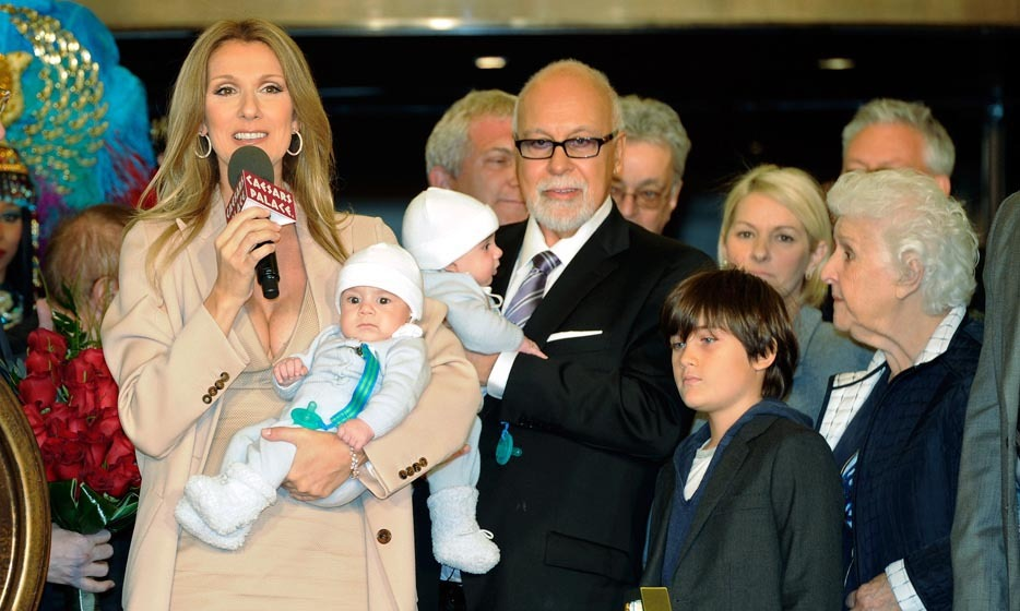"After the birth of her twins and a brief hiatus from show business, Celine was ready to return to the stage. Holding baby Nelson (with René nestling twin-brother Eddy), the Angélil family was greeted by throngs of fans as they arrived at Caesars Palace, where Celine was due to begin rehearsals for her new Vegas show. The songbird told 'HELLO!' exclusively that the babies, who were conceived after six IVF attempts, had made her life ""extraordinary."" (Photo © Getty Images)"
