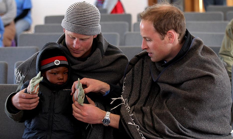 <p>The sweet brothers put gloves on a young boy during a visit to a child education centre in Lesotho.</p>