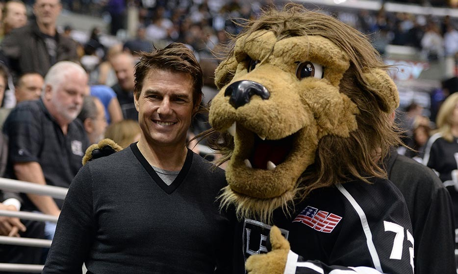 Tom Cruise posed for a photo with Bailey, the Los Angeles Kings mascot, at a game between the San Jose Sharks and the Kings in 2013. The 50-year-old star cheered on as the Kings won 3-0 in game five of the Western Conference semifinals. (Image: Harry How/Getty Images)