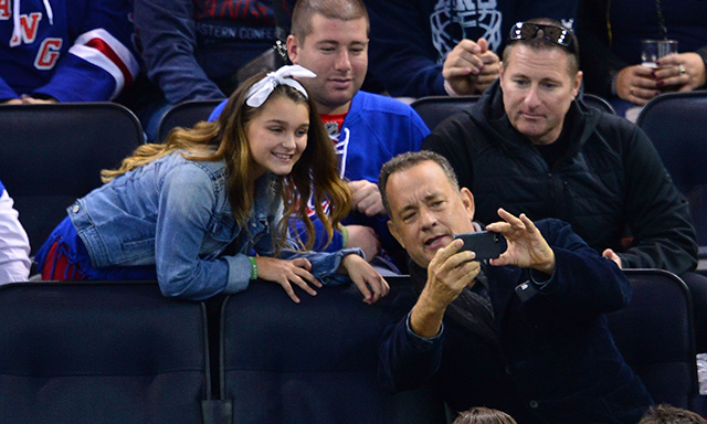 Tom Hanks obliges a teenaged fan with a selfie, also at the New York Rangers vs. Toronto Maple Leafs game on Oct. 12. Talk about a class act! (Photo: James Devaney/GC Images)