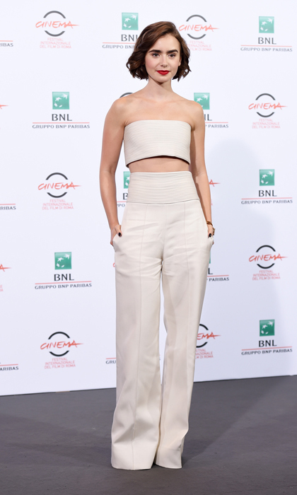 Lily Collins proved white has no expiration date in a super chic Pamella Rolan two-piece at the 'Love, Rosie' photocall in Rome. The actress finished off her effortless look with easy waves and a bold lip.