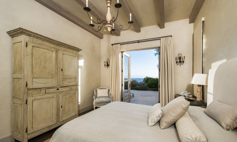 This guest bedroom is absolutely luxe and offers similar views of the beach and crystal-clear waters. A back door opens up onto the backyard's pristinely manicured landscaping. (Image: Zillow)