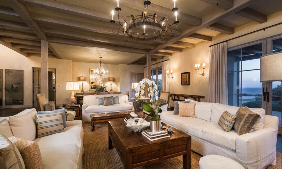 An iron, candleholder-style chandelier lights up a beautifully spacious living room, perfect for post-dinner chats and relaxation. (Image: Zillow)
