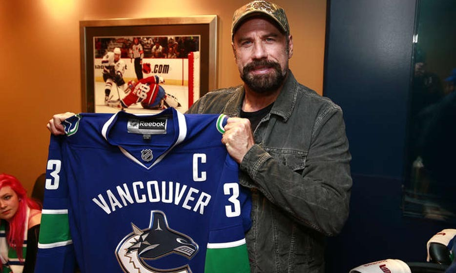 John Travolta was in Vancouver on Oct. 18, where he took in a game at Rogers Arena and cozied up to a Canucks jersey. (Photo: Jeff Vinnick/NHL via Getty Images)