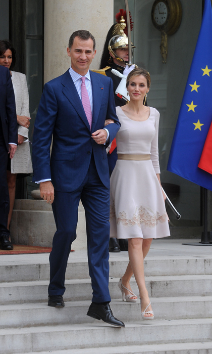 When in... France! With her king on her arm, Queen Letizia did Paris proud in a flirty, fitted dress with a nipped waistline and her hair slicked back. For colder climates, a similar dress would look great with a sleek bootie or glitzy gold pumps.