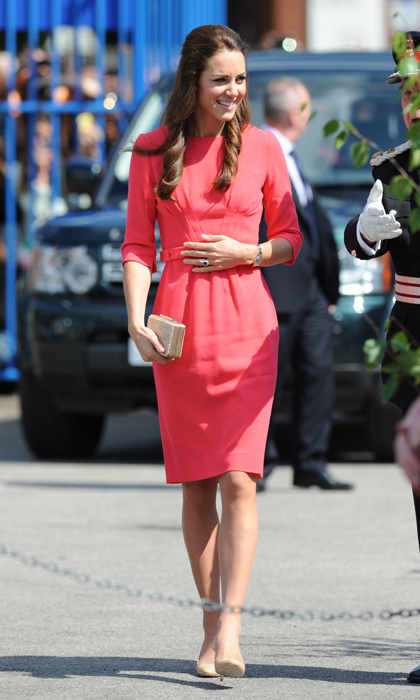 Before announcing her pregnancy, a chic and cheerful Duchess of Cambridge made an official school visit on July 1, 2014. The only thing we love more than her salmon-pink frock is her hairstyle: half of her locks slicked back and the rest cascading in shiny curls. <p>Photo: © Getty Images</p>