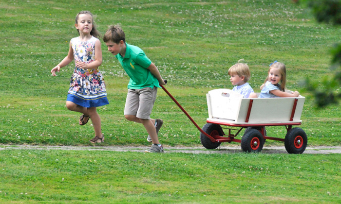 Older brother Christian playfully wheeled the twins along to the Danish royal family's summer photocall at Grasten Castle in July 2013. 