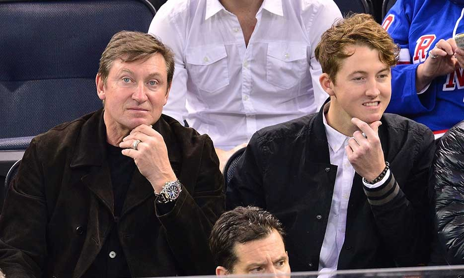Hockey great Wayne Gretzky and his son, Ty, shared a gesture as the Tampa Bay Lightning faced off against the New York Rangers in late 2014. (Photo by James Devaney/GC Images)