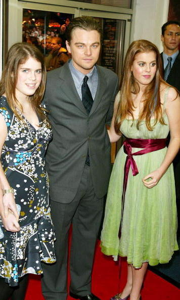 Leonardo DiCaprio kept a stoic pose while taking a picture with Princess Eugenie and Princess Beatrice at 'The Aviator' premiere in 2004.