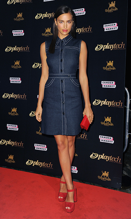 Model Irina Shayk struck a pose at the Playtech launch party in a retro-chic denim dress with contrast stitching and cherry-red suede platforms.
