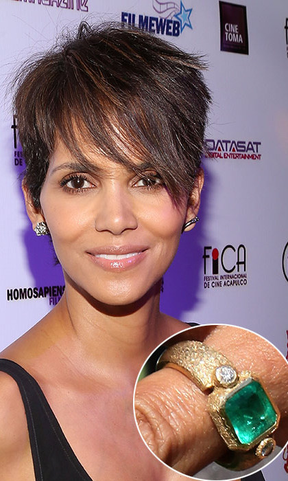 Olivier Martinez commissioned a unique piece of jewellery from his Paris neighbour, jeweller Robert Mazlo, to present to his actress love, Halle Berry. The ring features a central emerald flanked by two diamonds, set in a textured gold band.