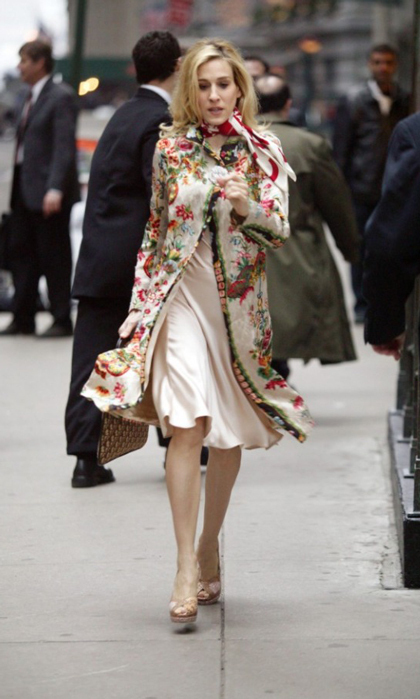 Braving the elements in a colourful floral coat paired with a red-and-white Chanel neck scarf.