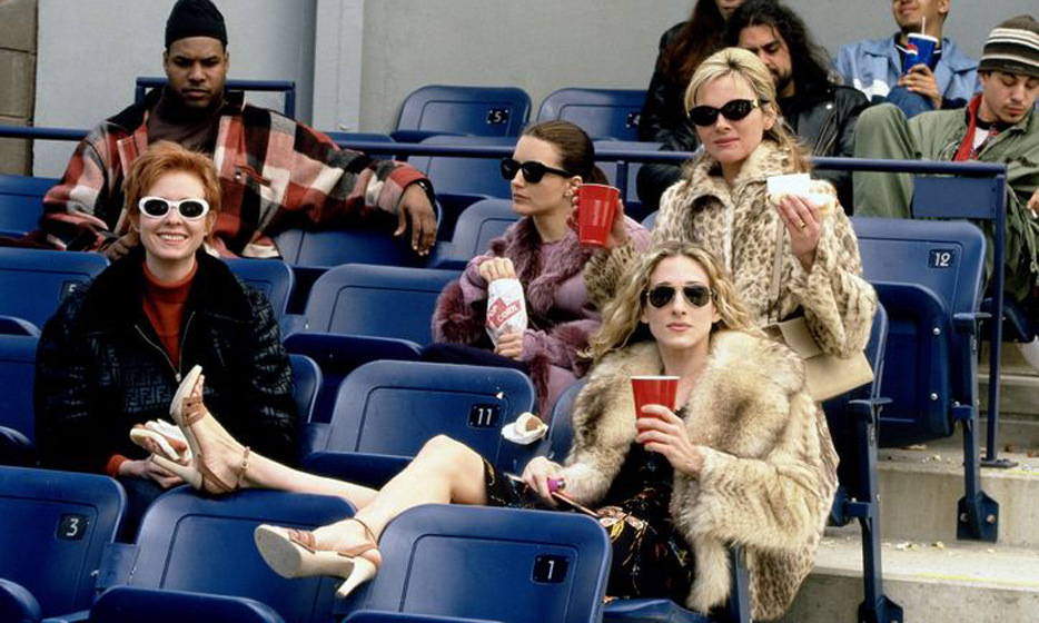 At the baseball game sporting high-heeled sandals, a fur coat and aviator sunglasses.