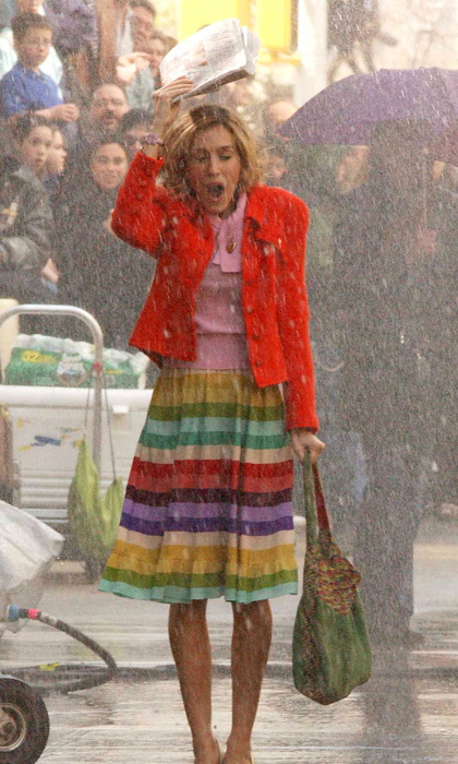 Braving the sudden downpour during a hot date with her city in a bold, rainbow-hued ensemble.