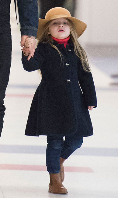 The ultimate mini fashionista in skinny jeans, a pea coat, Chelsea boots and a fedora hat while arriving at JFK airport with her family. Photo: © Splash