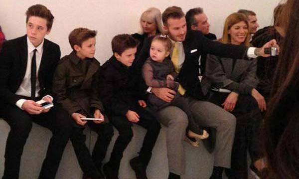 Sat front row of mum's 2014 fashion show with her brothers Brooklyn, Romeo and Cruz.