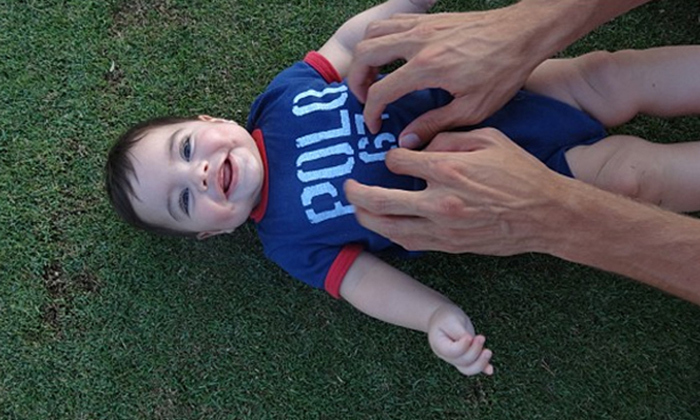 "…The second photo was a super-cute ""after"" shot, in which Milan was seen lying on the grass, laughing away and clearly full of glee as his father tickled him on the stomach.