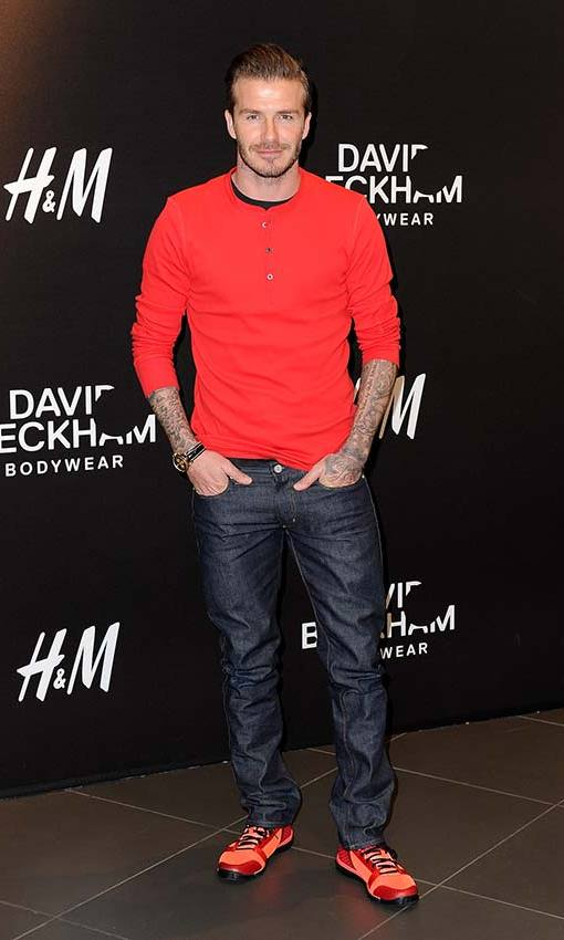 Adding a pop of colour in a red jumper for the launch of his H&M collection. Photo: © Getty Images