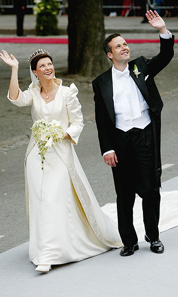 One year later, and the Norwegian royals were celebrating again at the wedding of Haakon's younger sister, Princess Martha Louise. The bride married author Ari Behn in May 2002 wearing a two-piece wedding outfit created for her by Oslo-based designer Wenche Lyche, which featured a dress and jacket. The costume was inspired by the shape and colour of the Martha lily and the Swarovski-embroidered bridal jacket was made of off-white duchess satin. The bride – whose bouquet consisted mainly of lilies – also paid tribute to her royal heritage by holding her veil in place with a tiara originally belonging to Queen Maud.