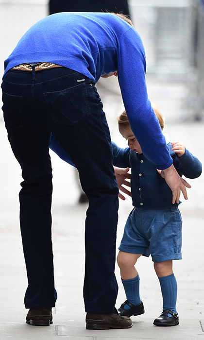 Overwhelmed by the crowds and camera flashes outside the Lindo Wing, Prince George seeks out the comfort of his father's embrace.