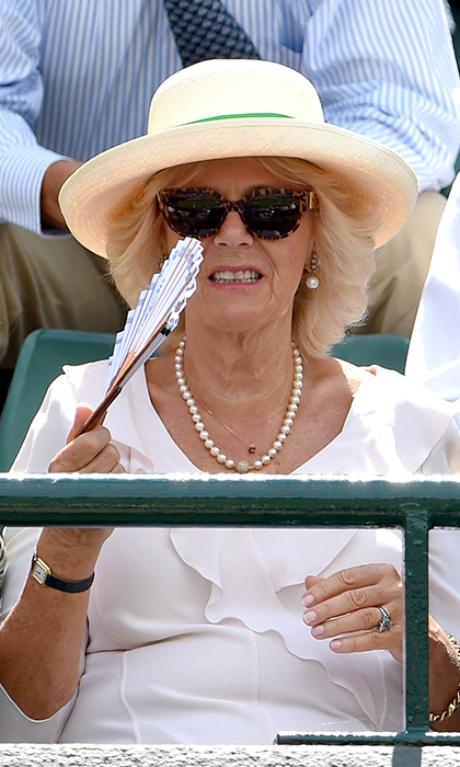 Camilla, Duchess of Cornwall, keeps cool with a fan.