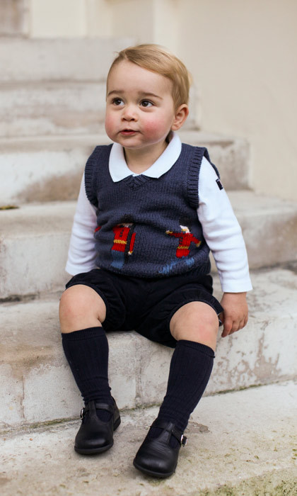 A rosy-cheeked Prince George sitting on the steps of Kensington Palace in his first solo official portrait.