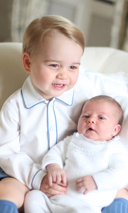 An extremely proud big brother holding his newborn royal sister.